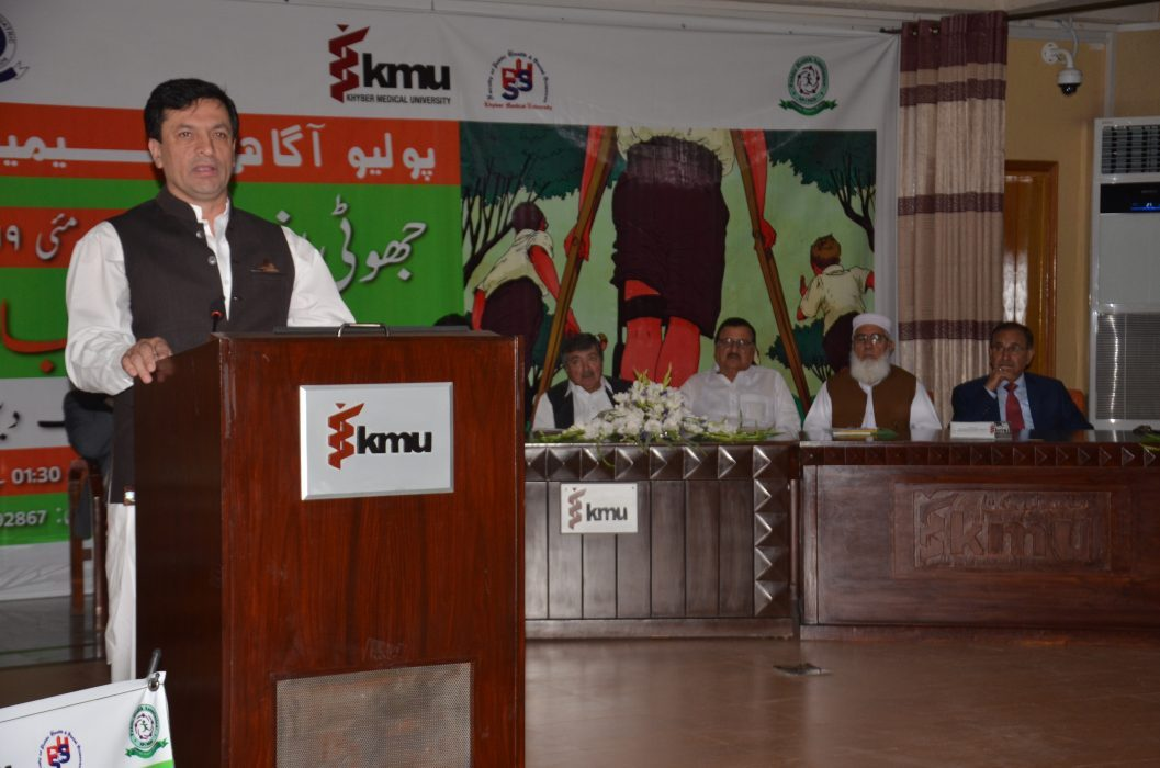 03.Secratary-Health-KP-Dr-Faruq-Jamil-talking-to-Polio-Agahi-Seminar-organized-by-KMU-and-PHA-VC-KMU-Dr-Arshad-Javaid-along-with-others-also-sitting-on-stage-e1557927128425.jpg